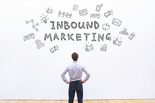 "An inbound marketing expert stood looking at a mural that reads ""inbound marketing."""