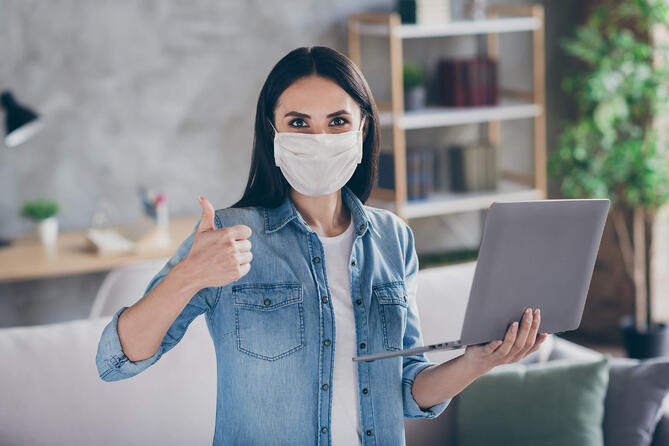 Woman wearing a Face Mask holding a Lap Top