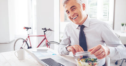 Business man eating healthy lunch with bike in background