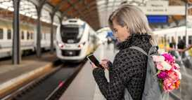 woman using WiFi on phone at train station