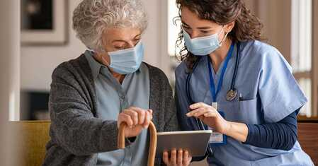 nurse and care home resident using a tablet