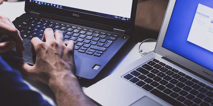 man using two laptops