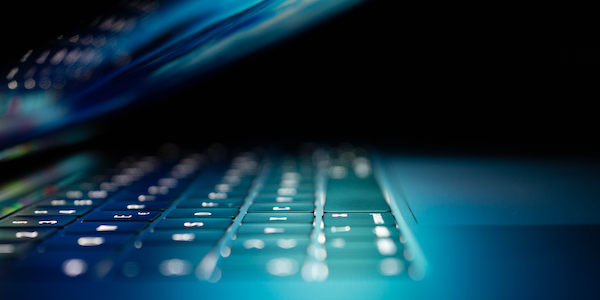 Laptop keyboard lit up in the dark