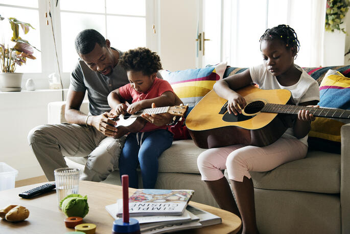 Black father on the couch with two young daughters who both have guitars as he teaches them to play guitar