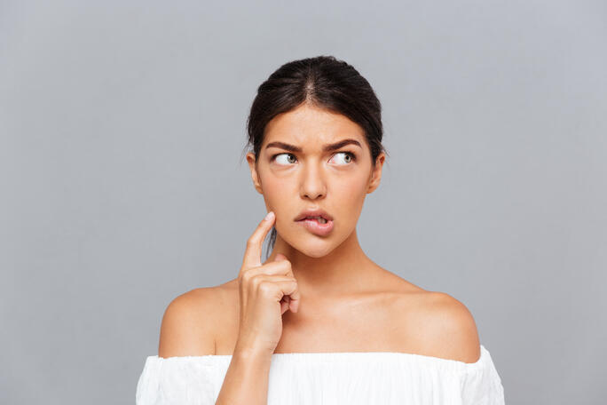 woman thinking with index finger on her cheek and eyes looking sideways