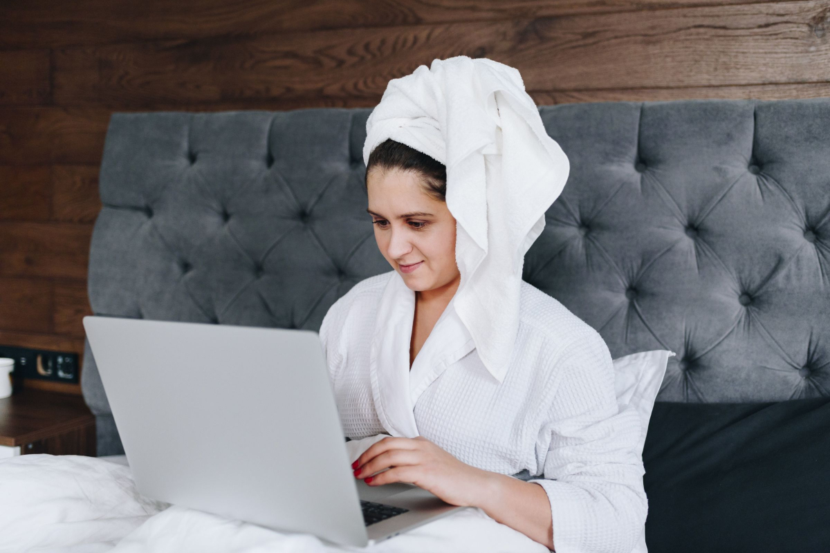 Woman applying for job on virtual event in her bathrobe and towel