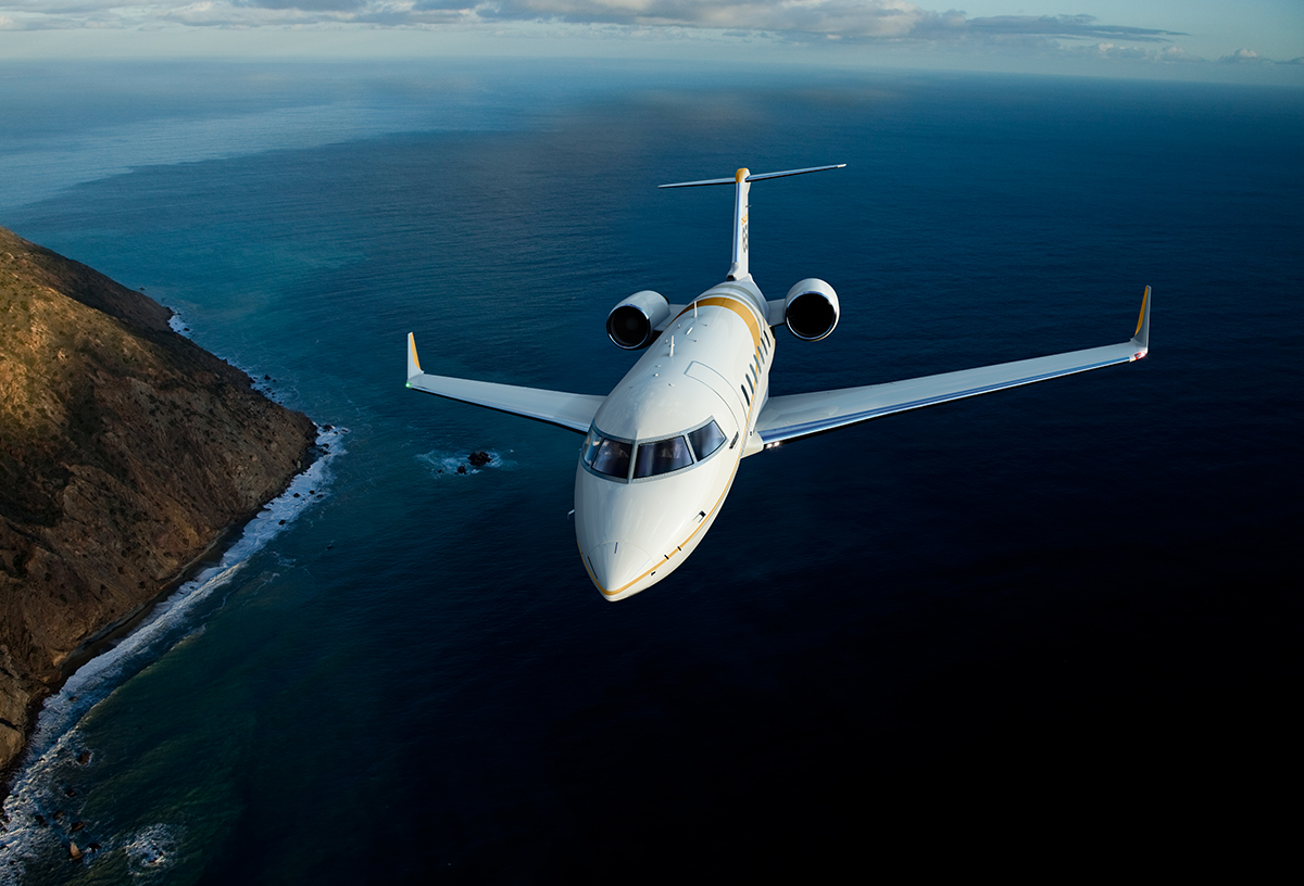 bombardier challenger 650 in flight over water
