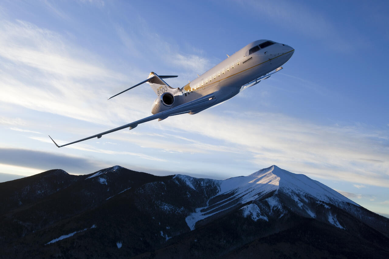 bombardier global 5000 above mountain peak