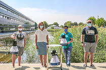 "Dr. Silke Göttler of the Biogents AG (Regensburg) and members of HNU's DigiHealth Institute with a ""BG-Trap Station"" including an electronic mosquito counting module (in front) and two mobile BG-Pro traps at the HNU lake."