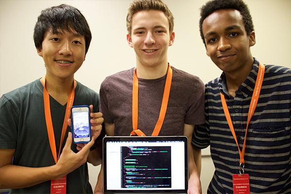 three students showcasing work