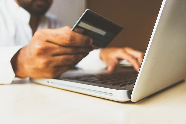 man holds credit card next to laptop