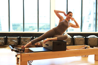 man performning pilates for beginners on a pilates reformer