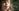 small child girl holding a dandelion and blowing on it