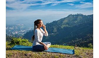 young woman practices breathing techniques sitting in lotus pose outdoors