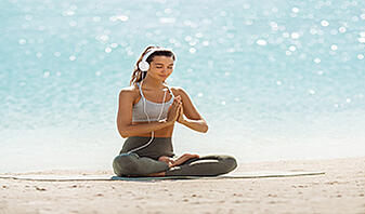 woman in yoga meditation pose with headphones on the beach listening to yoga music