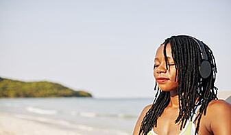 woman relaxing on the beach listening to meditation music
