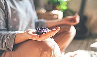 young woman is meditating with a crystal doing chakra meditation