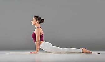 young woman practicing kundalini yoga cobra pose