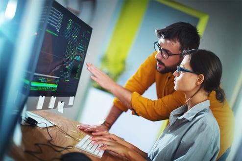 En dame peker på en dataskjerm mens en mann henger over skulderen hennes og ser på.
