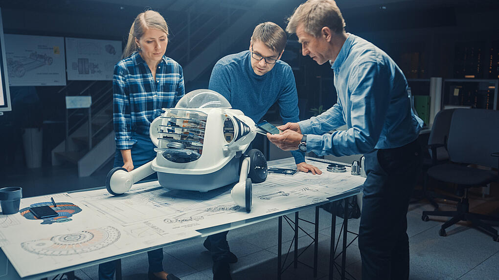 3 enginers are checking the robot, Common startup mistake: over-engineering in early design