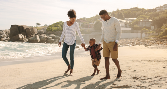 Family on beach vacation budgeting