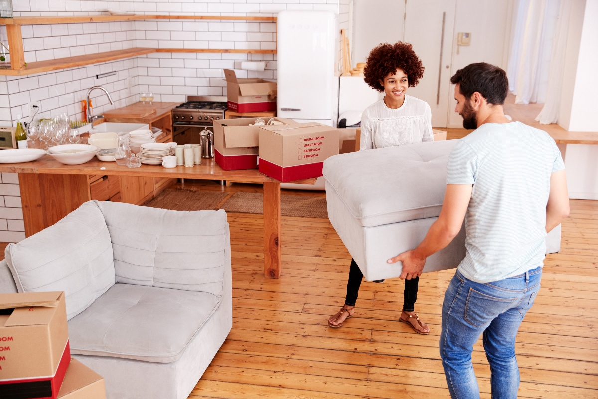 couple moving furniture into new home