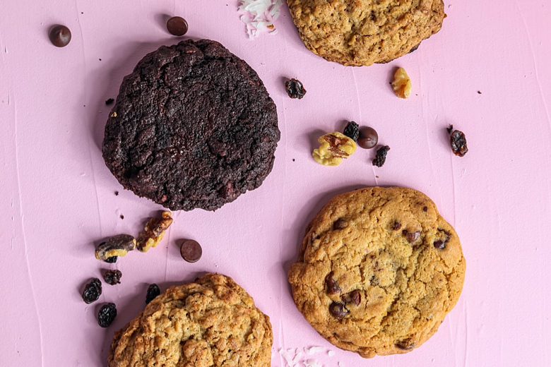 Flat lay of different coloured cookies on a pastel pink background