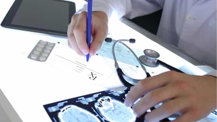 medico revisando una radiografia del cerebro y anotando en un papel