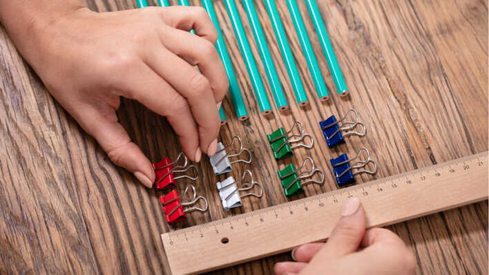 mujer ordenando objetos por color y tamaño con el uso de una regla