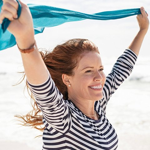 mature woman holding scarf to the wind