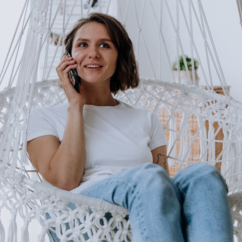 woman in white shirt and blue jeans sitting in chair while using phone
