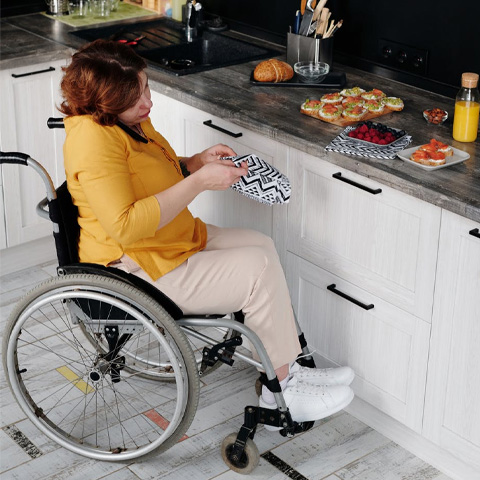 woman in yellow t shirt sitting in wheel chair preparing food in kitchen