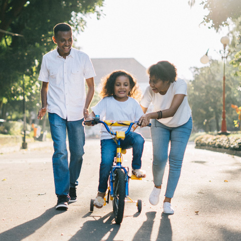 parents teaching daughter how to ride bike