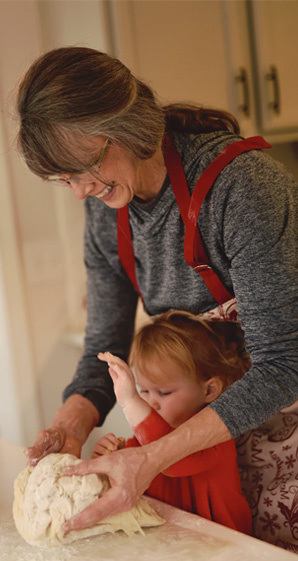 woman flouring dough with child