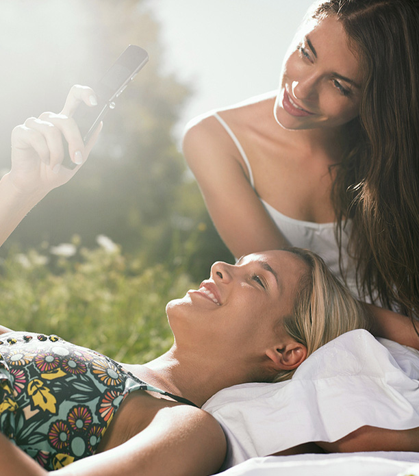 two woman sitting in meadow using mobile phone