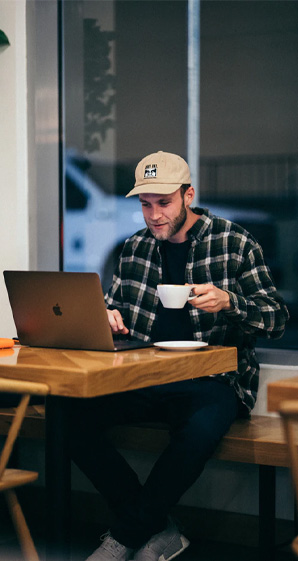 man sitting while having coffee on his laptop
