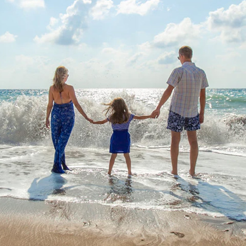 man, woman and child holding hands on the beach