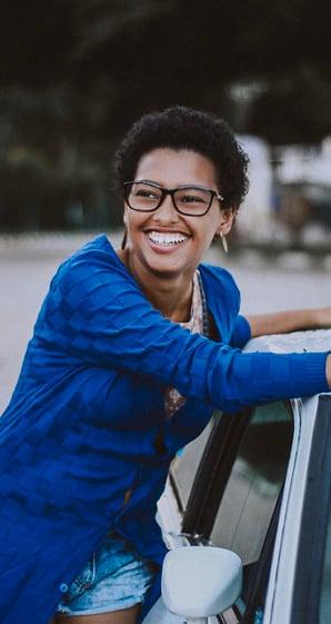 woman smiling besides car