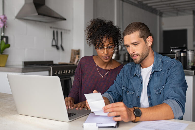 male and female look at bills in front of computer