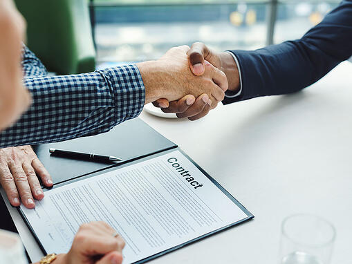 two men shaking hands over signed contract