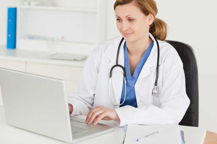 Female doctor working on her laptop in her office