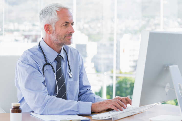 Doctor typing on his computer in the office