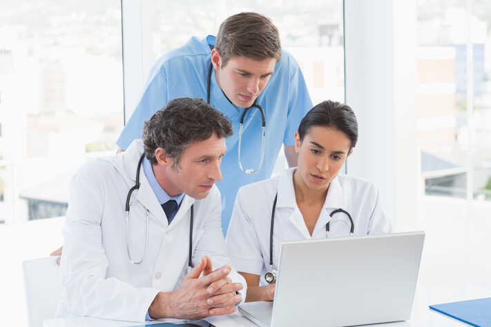 Team of doctors working on laptop computer in medical office-1