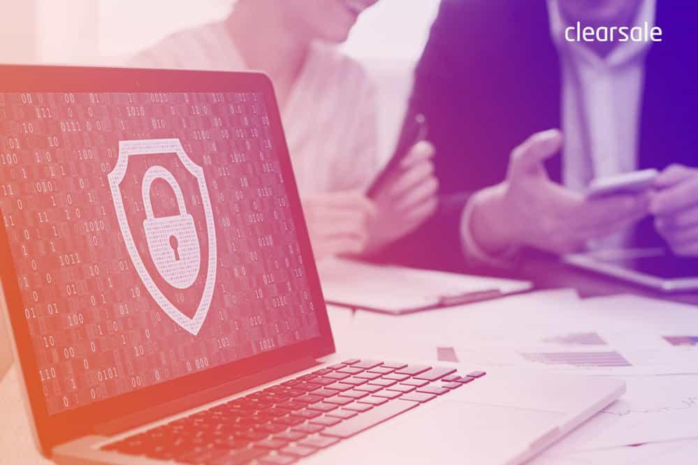 Duas pessoas mexendo no celular ao fundo e um notebook aberto com o símbolo de cadeado, representando a cibersegurança, em foco