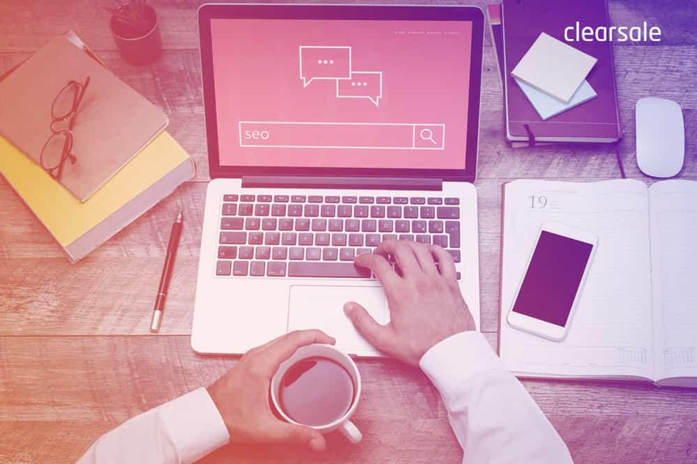Mãos de um homem fazendo uma busca no notebook sobre seo para ecommerce ao lado de cadernos, caneta, celular, óculos e uma xícara de café