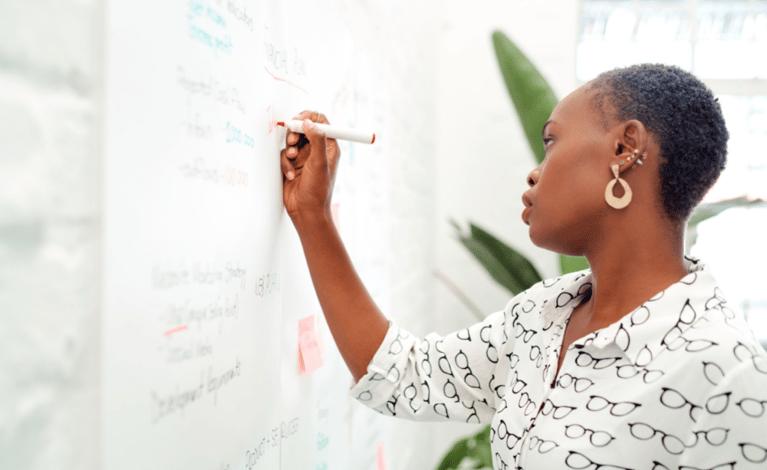 black woman writing on dry erase board