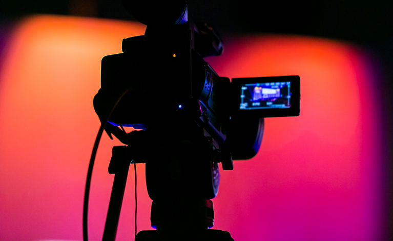 Video camera recording event on a pink purple background