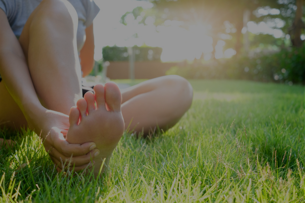 Barefoot woman sitting on the green grass thinking about athletes foot infection