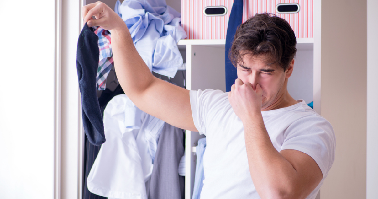 Man smelling his sweaty clothes before washing them to avoid a fungal infection