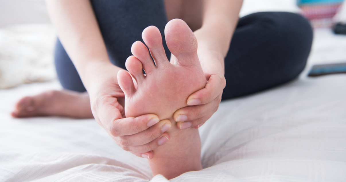 Woman touching her foot sitting on the floor worried about athletes foot symptoms